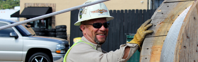 Covington Electric Department employee smiling at camera while steadying spool of electrical wire