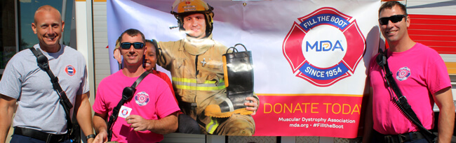 3 CFD firefighters standing in front of MDA banner